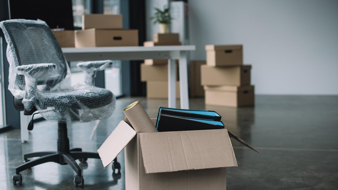 Büro mit Umzugskisten und verpacktem Bürostuhl