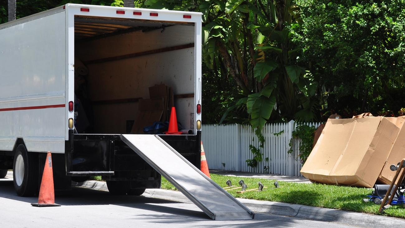 großer Transporter mit Absperrung beim Umzug vor einem Grundstück