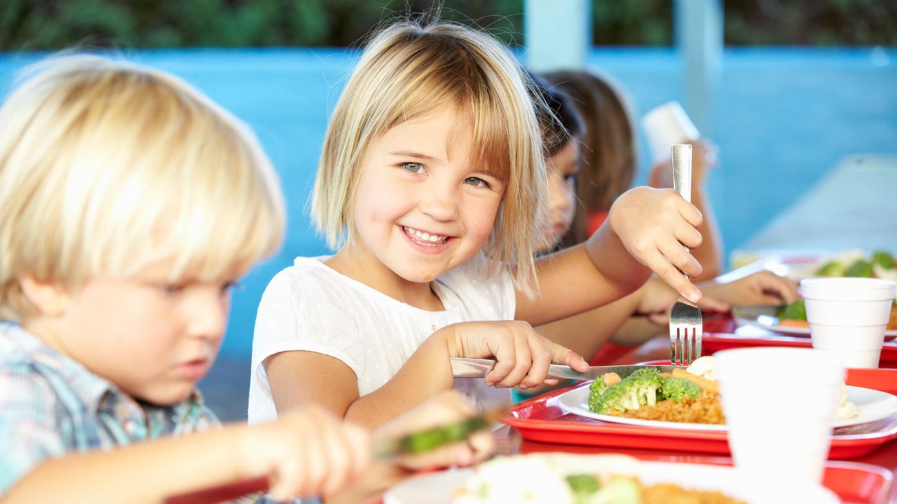 lachendes Mädchen beim Mittagessen im Kindergarten